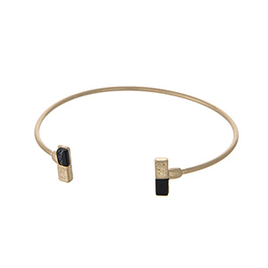 Dainty gold tone cuff bracelet with black natural stones.