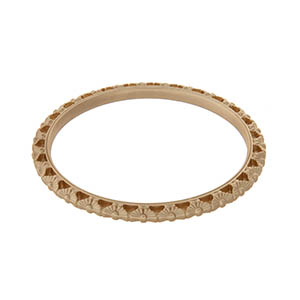 "Gold tone bangle bracelet with a cutout floral decor. Opening is 2.5"" wide."