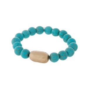Turquoise natural stone beaded stretch bracelet with a hammered gold tone piece.