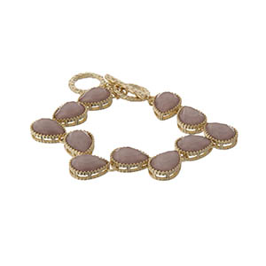 """Gold tone adjustable toggle bracelet with rose pink teardrop stones. Approximately 9"""" in length."""