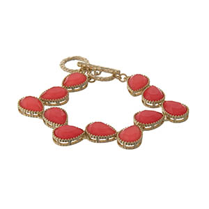 "Gold tone adjustable toggle bracelet with neon coral teardrop stones. Approximately 9"" in length."