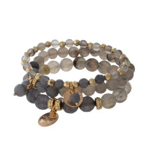 Gray beaded stretch bracelet set with a gold tone charm.