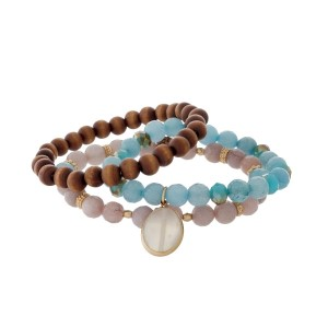 Three piece beaded stretch bracelet with wooden, light blue and pink beads.