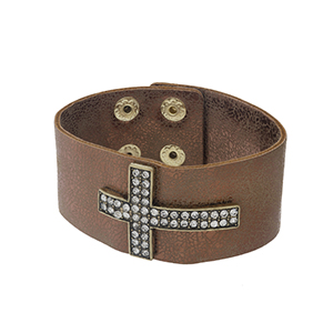 "Bronze faux leather snap bracelet with a rhinestone gold tone cross. Approximately 8"" in length."