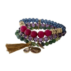 Purple, green and burgundy beaded bracelet set with gold tone and tassel charms.