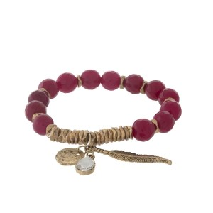Crimson and gold tone beaded stretch bracelet with a leaf charm.