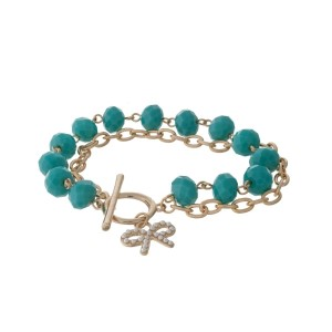 Gold tone toggle bracelet with turquoise faceted beads and a bow charm.