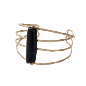 Gold tone hammered cuff bracelet with a black stone focal.