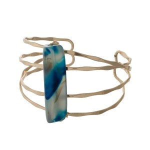 Gold tone hammered cuff bracelet with a blue stone focal.