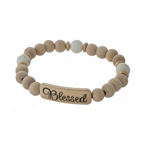 """Ivory beaded stretch bracelet with a hammered gold tone bar stamped with """"Blessed."""""""
