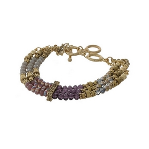 Gold tone, three row toggle bracelet with purple, gray and iridescent beads.