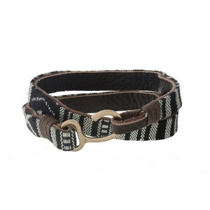 Leather wrap bracelet with black and white patterned fabric and a hook closure.