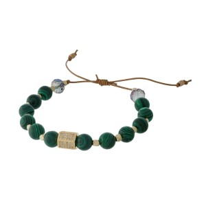 Adjustable cord bracelet with green malachite natural stone beads, gold tone square beads, and clear rhinestones. Handmade in the USA.