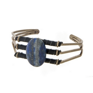Burnished gold tone cuff bracelet with black leather and a lapis oval stone.