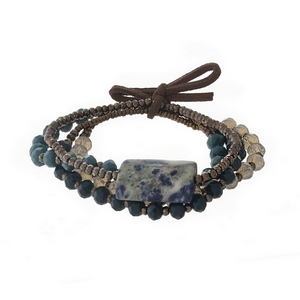 Four piece stretch bracelet set with bronze, teal and white opal beads and held together by a suede bow.
