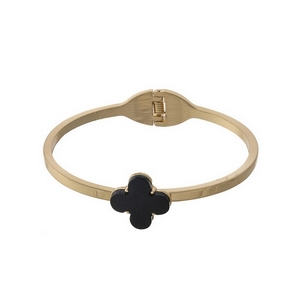 Gold tone, hinge bangle bracelet with a black clover focal.