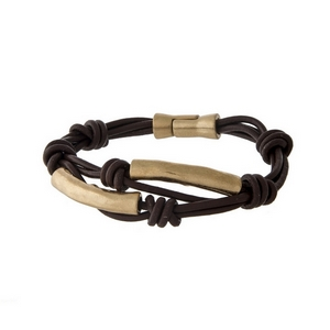 Brown leather bracelet with two gold tone bars and a magnetic closure.