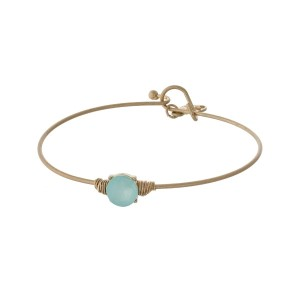 Dainty gold tone bracelet with a wire wrapped mint green circle stone.