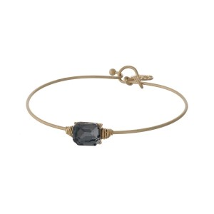 Dainty gold tone bracelet with a wire wrapped black rectangle stone.
