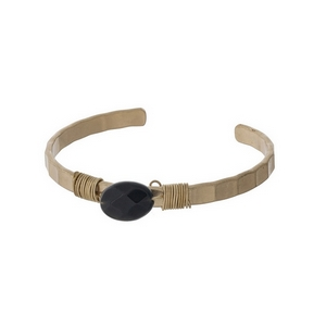 Gold tone cuff bracelet with a wire wrapped black stone.