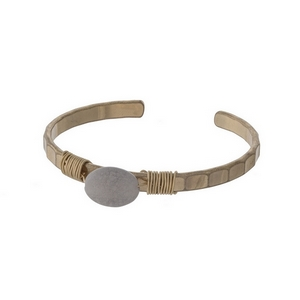 Gold tone cuff bracelet with a wire wrapped gray stone.