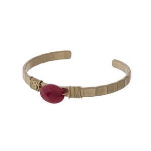 Gold tone cuff bracelet with a wire wrapped red stone.