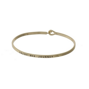 "Gold tone, dainty bangle bracelet stamped with ""Enjoy the journey."""