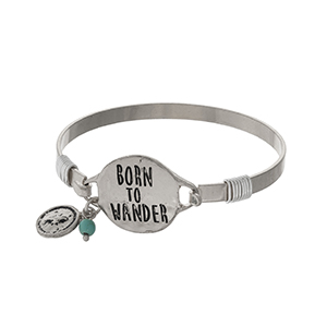 "Silver tone bangle bracelet stamped with ""Born to Wander"" and accented with a small compass charm."