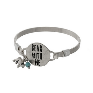 """Silver tone bangle bracelet with a circle focal, stamped with """"Bear With Me"""" accented with a turquoise bead."""