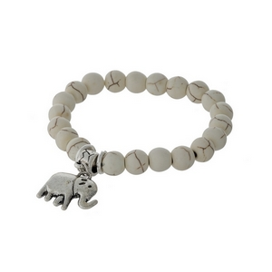 Ivory natural stone beaded stretch bracelet with a silver tone elephant charm.