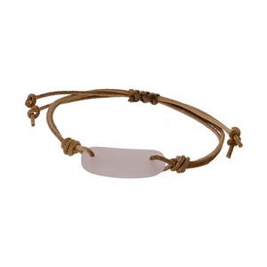 Adjustable brown cord bracelet with a pink stone.