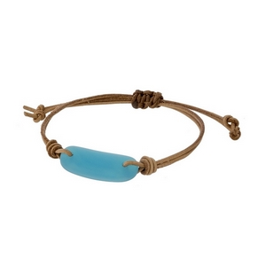 Adjustable brown cord bracelet with a turquoise stone.