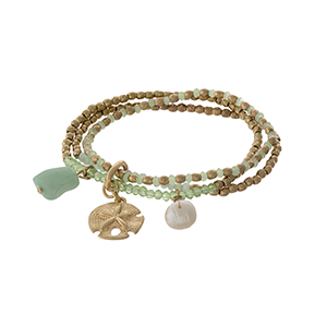 Gold tone and mint green beaded stretch bracelet with a sand dollar charm.
