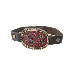 Brown leather snap bracelet with a gold tone focal, accented with red rhinestones.
