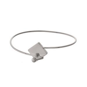 Dainty silver tone bangle bracelet with a geometric hook clasp.