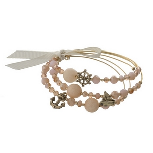 Gold tone cuff bracelet set with peach beads and nautical charms.