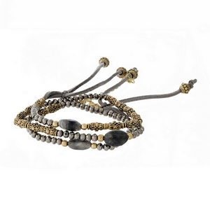 Gray faux suede and beaded stretch wrap bracelet with gold tone accents and a lobster clasp closure.
