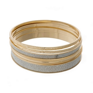 Four piece gold tone bangle set with silver glitter accents.