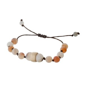 Brown cord bracelet with peach natural stone beads, a gold tone bead accents and a pull-tie closure.