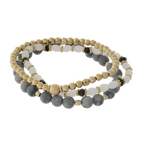 Three piece stretch bracelet set featuring gray jasper natural stone beads, gold tone beads, and white opal faceted beads.