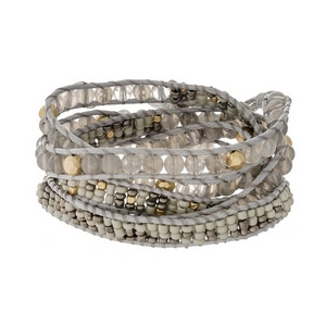 Gray cord wrap bracelet featuring gray faceted and natural stone beads, gold tone accents and a button closure.