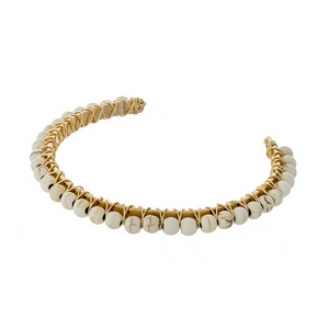 Gold tone cuff bracelet with wire wrapped ivory beads.
