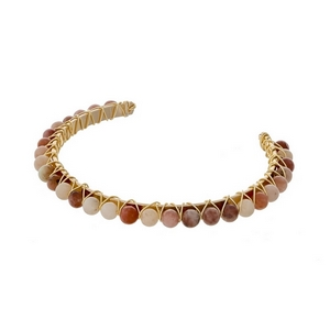 Gold tone cuff bracelet with wire wrapped peach and ivory natural stone beads.
