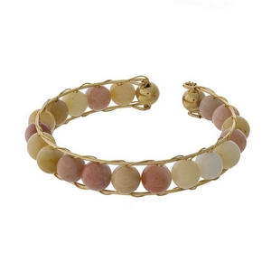Gold tone cuff bracelet featuring wire wrapped peach beads.