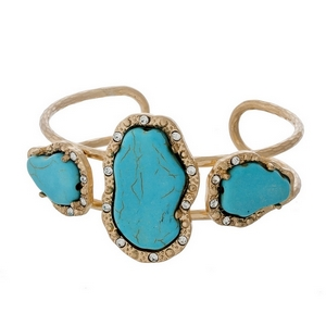 Matte gold tone cuff bracelet displaying three turquoise natural stones accented with clear rhinestones.