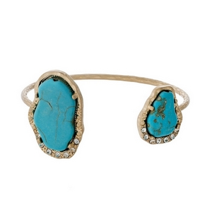 Matte gold tone cuff bracelet displaying two turquoise natural stones accented with clear rhinestones.