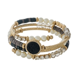 Gold tone coil bracelet featuring pearl beads, gray faceted beads, and a black faux druzy stone.