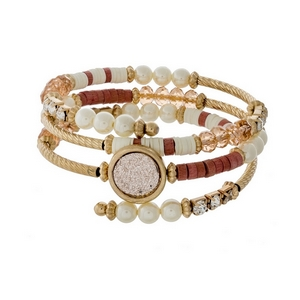 Gold tone coil bracelet featuring pearl beads, pink faceted beads, and a pink faux druzy stone.