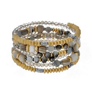 Coil bracelet featuring gray faceted beads and gray chip stones with gold tone accents.