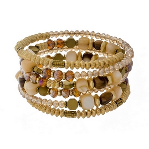 Coil bracelet featuring topaz faceted beads and neutral colored chip stones with gold tone accents.